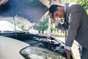 Man looking under the hood of car
