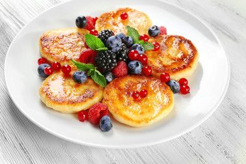 Fritters of cottage cheese with berries in plate on wooden table, closeup