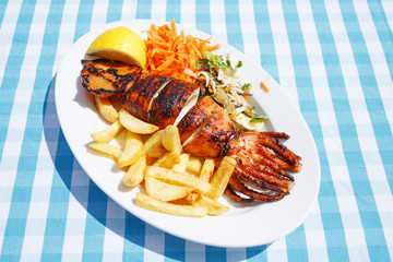 Lunch calamari/Grilled calamari in plate with potato and vegetables in restaurant on beach. Plaid cloth background.