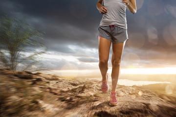 Woman runs in a rocky landscape