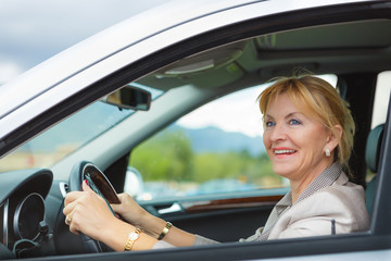 Beautiful smiling elderly woman 55-60 years with white teeth in suit at the whee, Driving a Car Through the mountains