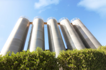 higher steel silos with green plants