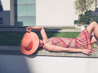 Young woman relaxing outside apartment block