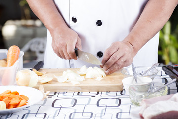 Chef cutting the onion on a wooden board