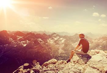 Male hiker sitting on a mountain summit on sunset