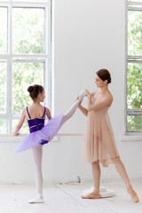 The little ballerina posing at ballet barre with personal
