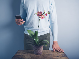 Young man with phone and orchid