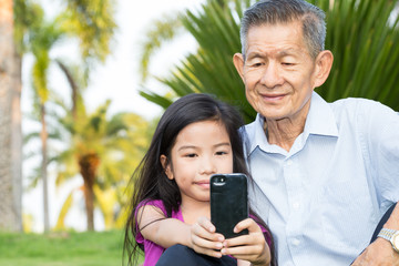 Grandfather and grandchild making selfie with smart phone in the
