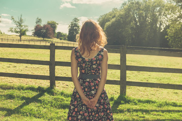 Young woman standing in field by fence on summer day
