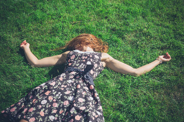 Young woman lying in the grass on a summer day