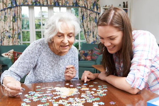 Teenage Granddaughter Helping Grandmother With Jigsaw Puzzle