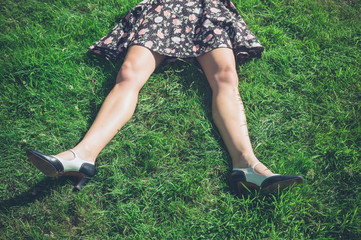 Legs of young woman lying on grass in field