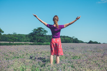 Woman raising her arms in a field of purple flowers
