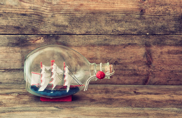 image of decorative boat in the bottle on wooden table. nautical concept