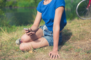 Wall Mural - Young woman using smart phone by water in park