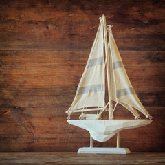 old vintage wooden white sailing boat on wooden table.