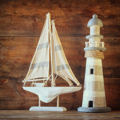 old vintage wooden lighthouse and sailing boat on wooden table