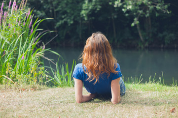 Young woman relaxing by water in park
