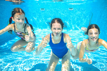 Family swim in pool underwater, happy active mother and children have fun in water, sport