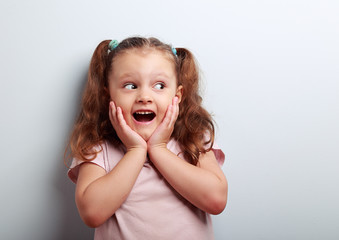 Fun surprising kid girl with open mouth looking on empty copy sp