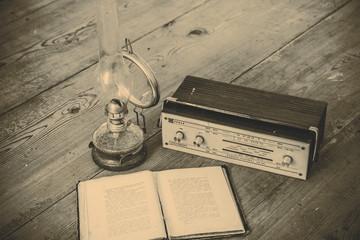 kerosene lamp and radio and book