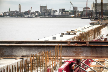 Construction works at the docks of the Schelde river with the Antwerp skyline in the background