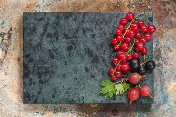 Summer berries on metallic background with space for text. Red currants, black currants and gooseberries