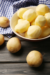 Peeled new potatoes in bowl on wooden table with napkin, closeup
