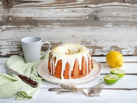 Moist lime and lemon bundt yoghurt cake, white rustic wooden