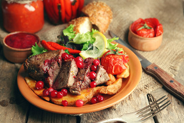 Tasty roasted meat with cranberry sauce, salad and roasted vegetables on plate, on wooden background