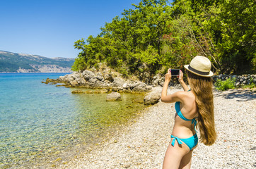 Young attractive girl taking photo on tropical beach