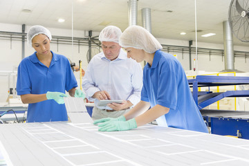 Businessman and technicians arranging solar cells to form solar panel on production line