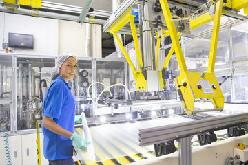 Factory floor worker smiling at camera and coating glass for solar panel assembly on production line
