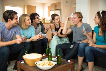 Group crowd of people friends at home in dorm playing games cards poker excited