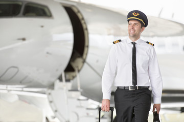 Smiling pilot walking away from private jet with suitcase