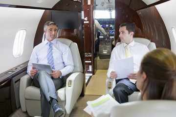 Businesswoman and Businessmen with digital tablet having meeting on private jet