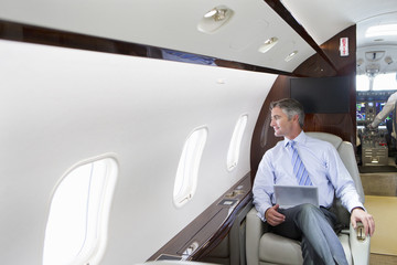 Businessman with digital tablet looking out of window on private jet