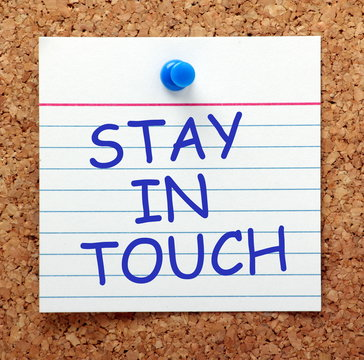 The phrase Stay in Touch in blue text on an index card pinned to a cork notice board as a reminder