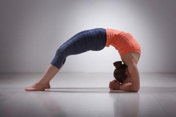 Beautiful sporty fit yogi girl practices yoga asana viparita dan