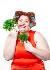 the fat woman wit red lipstick in curlers on a diet holding parsley and dill to eat isolated on the white background