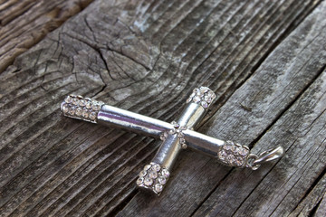 Silver christian cross on wooden background