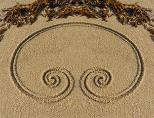 Esoterische Doppelspirale auf feinem Kies mit Tang als Ornament