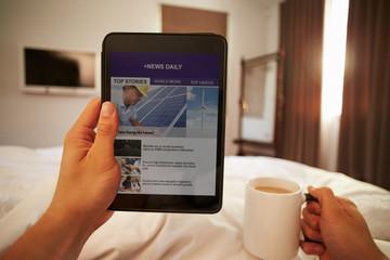 Man In Bed Looking At News Website On Digital Tablet