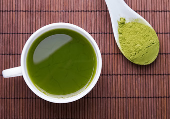 Wall Mural - Matcha tea in a white cup on the brown mat
