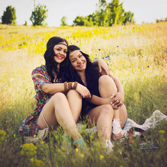 Two happy boho sisters hugging sitting outdoors
