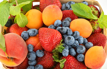 Strawberries, apricots, blueberries, peach and mint isolated on