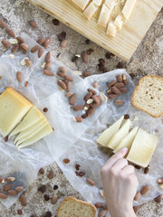 Woman hand holding a piece of cheese of snack of cheese, roasted bread and almonds