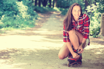 Girl going rollerblading sitting putting on in line skates outdo