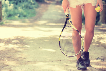 Cropped image legs of sportswoman with racket walking in park