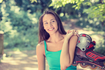 portrait happy young woman going rollerblading holding in line s
